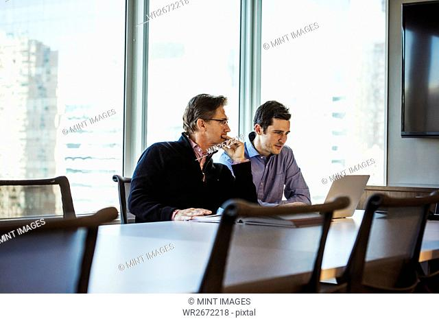 Two men at a table in a meeting room looking at a laptop computer