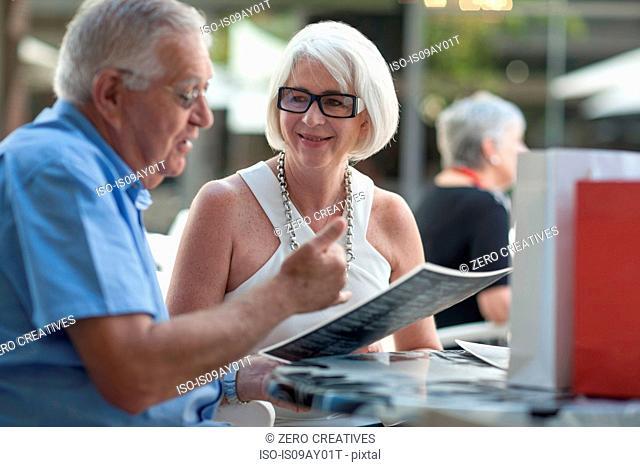 Senior man and woman reading menu at sidewalk cafe
