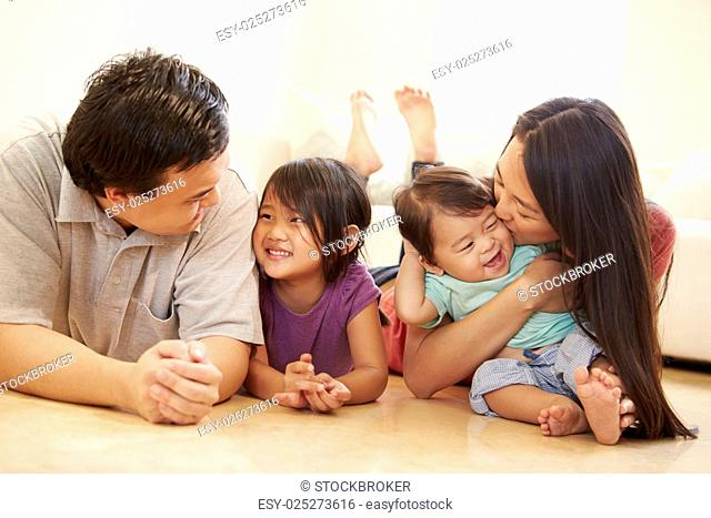 Portrait Of Family Lying On Floor At Home