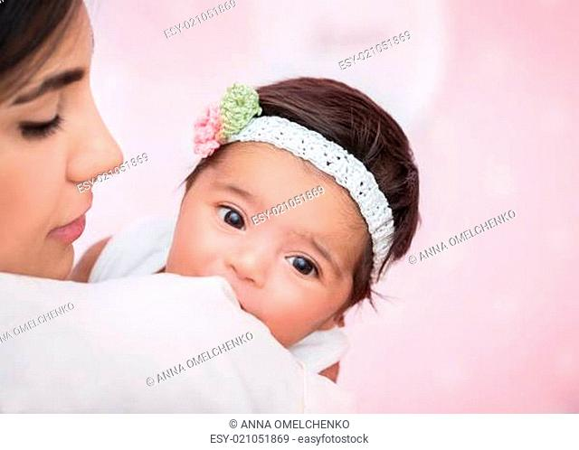 Closeup portrait of cute adorable little baby girl peeking over his shoulder mother, wearing nice head accessory, happy young family concept