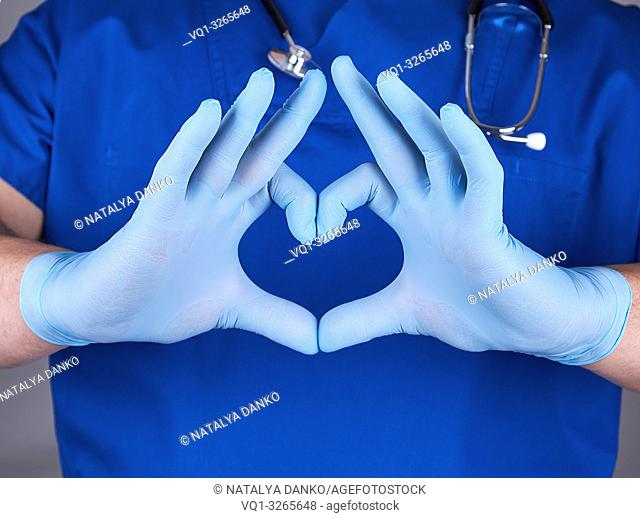 doctor in blue uniform and old latex gloves showing heart gesture, close up