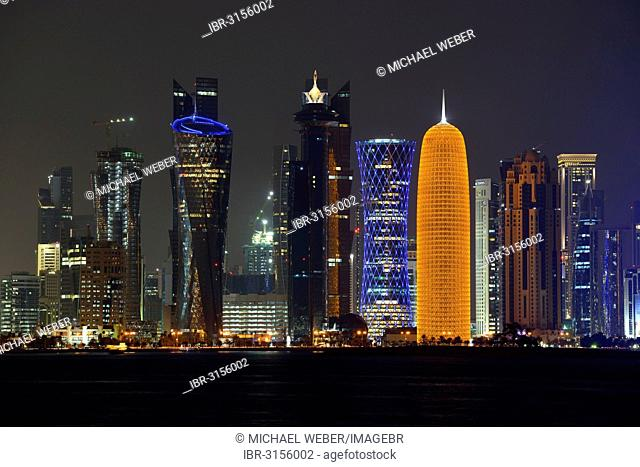 Skyline of Doha at night with the Al Bidda Tower, Palm Tower 1 and 2, the World Trade Center, Tornado Tower and the Burj Qatar Tower with golden illuminations