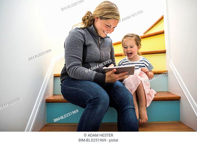 Caucasian mother and daughter using digital tablet on staircase