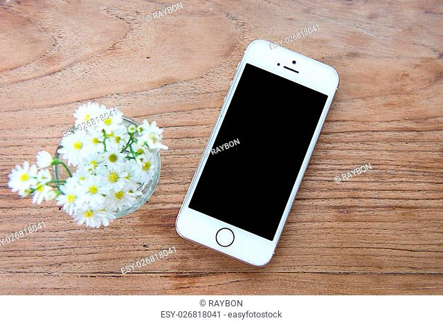 Smart phone with blank screen lying on wooden table, iphon style