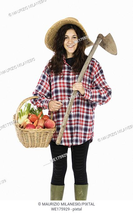 Young farmer with one arm holding a basket with fruit and vegetables, with the other a hoe, she is wearing a straw hat, checked shirt and green rubber boots