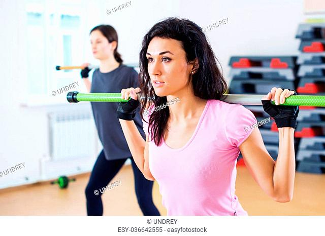 Group of people excercising with bars in gym doing squatting with a barbell at fitness club