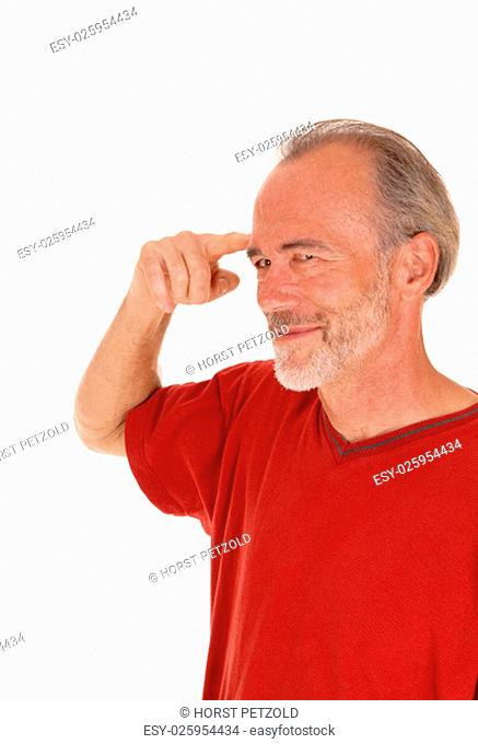 A closeup image of a middle age man pointing with his finger at his forehead.smiling, isolated for white background.
