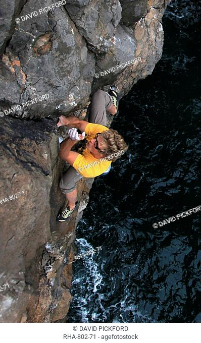 A climber deep water soloing above the sea on the limestone cliffs near St. Govan's Head, South Pembrokeshire, Pembrokeshire Coast National Park, Wales
