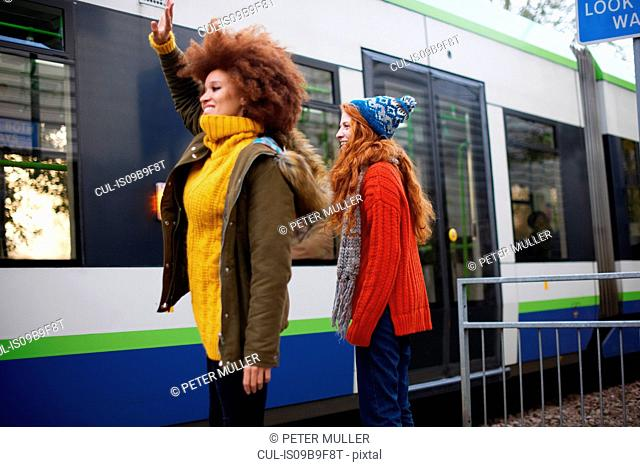 Friends waving at railway carriage