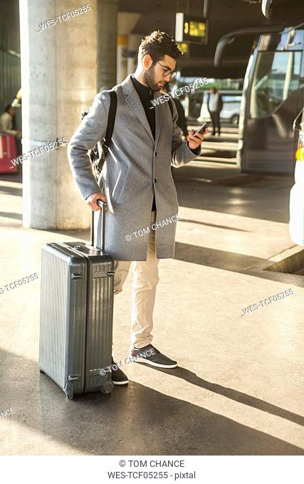 Businessman with baggage standing at bus terminal looking at cell phone