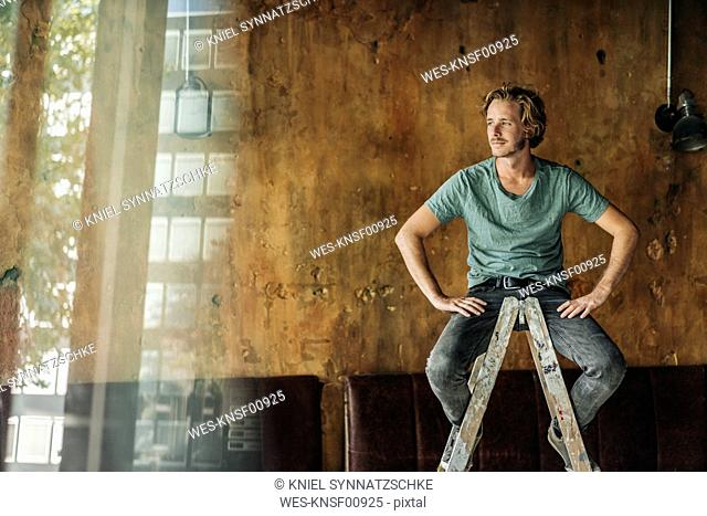 Man sitting on stepladder in unfinished room