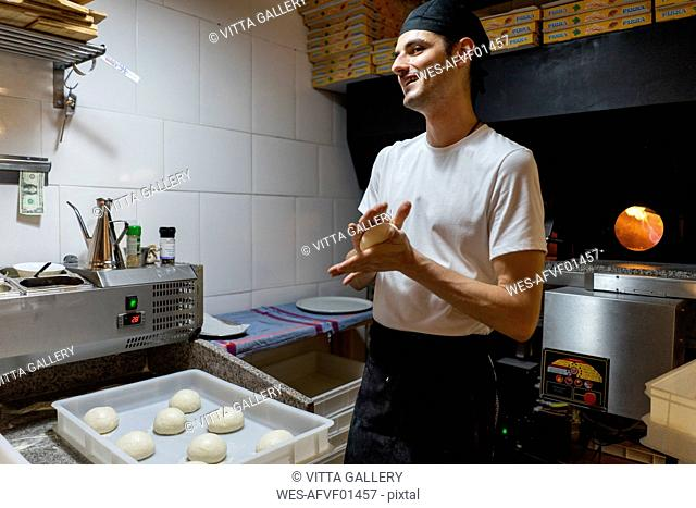 Smiling pizza baker shaping dough in kitchen