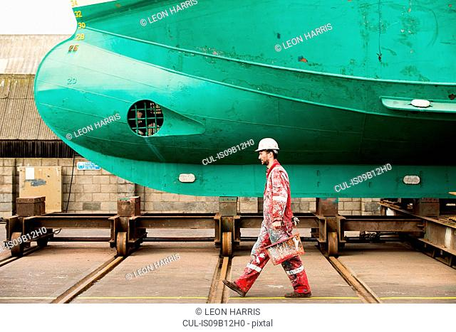 Male ship painter carrying paint cans in ship painters yard