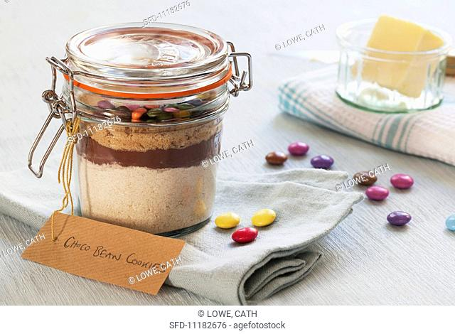A preserving jar containing the dry ingredients for making chocolate biscuits with chocolate beans