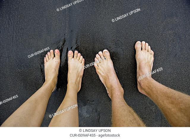 Pairs of male and female feet on black sand