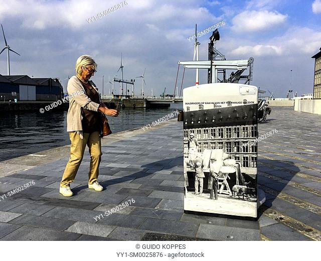 Antwerp, Belgium. Mature adult, caucasian woman capturing a photography covered object, decorating a harbour dock square