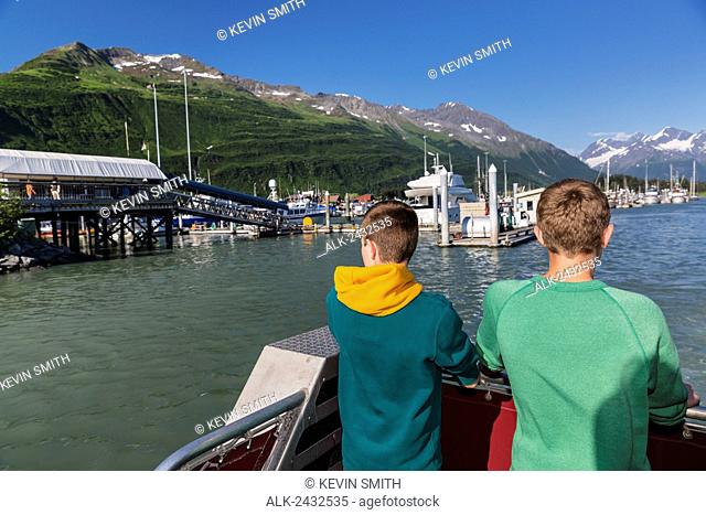 Two teens stand on the deck of a boat overlooking the Valdez small boat harbor and the Chugach Mountains, Prince William Sound, Southcentral Alaska