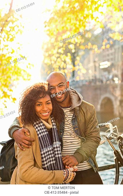Portrait smiling, affectionate couple hugging along sunny autumn canal