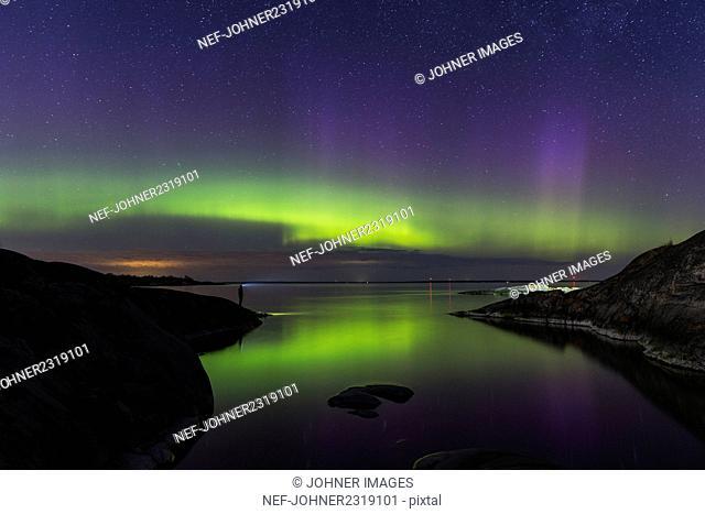 Man looking at northern lights above sea
