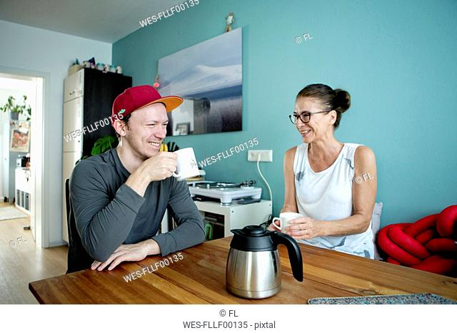 Mother and son sitting at the kitchen table, drinking coffee