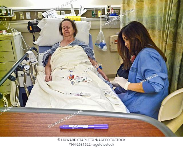 A nurse attends a mature woman patient in hospital prior to surgery