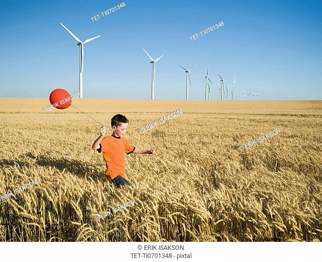 Boy running with balloon on wind farm