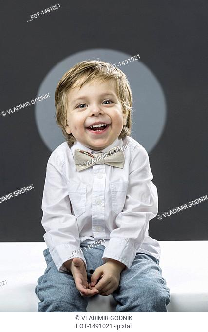 Portrait of cheerful boy with bowtie sitting against gray background