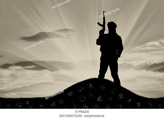 Concept of terrorism. Silhouette of a terrorist with a rifle standing on a pile of skulls at sunset