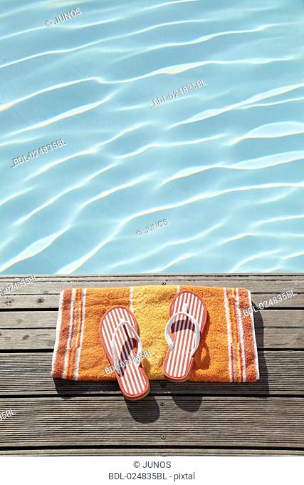 flip flops on towel at swimming pool