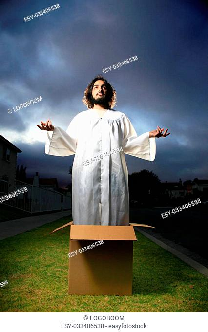 Man looking like Jesus standing in the box with hands raised