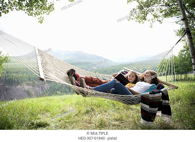 Sisters laying in rural hammock reading book