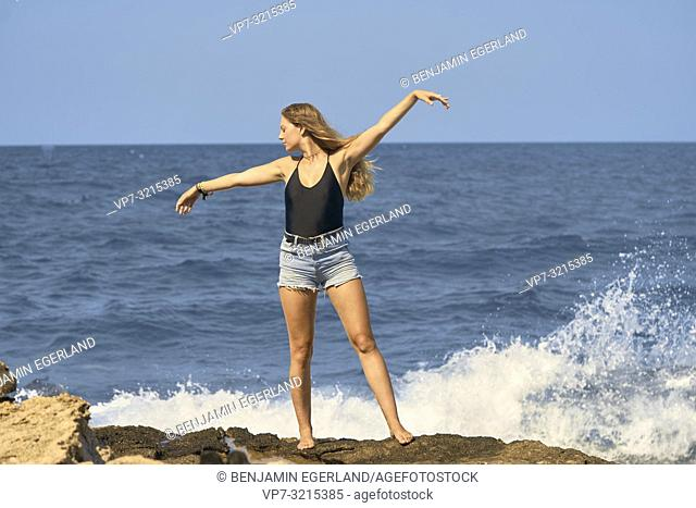 young woman stretching arms at seaside enjoying summer holiday and freedom, in Crete, Greece