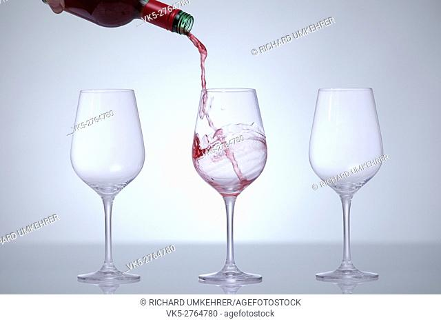 Motion picture of a man hand fill a glass with wine. Three glasses in a row. Against a white background and a vignette