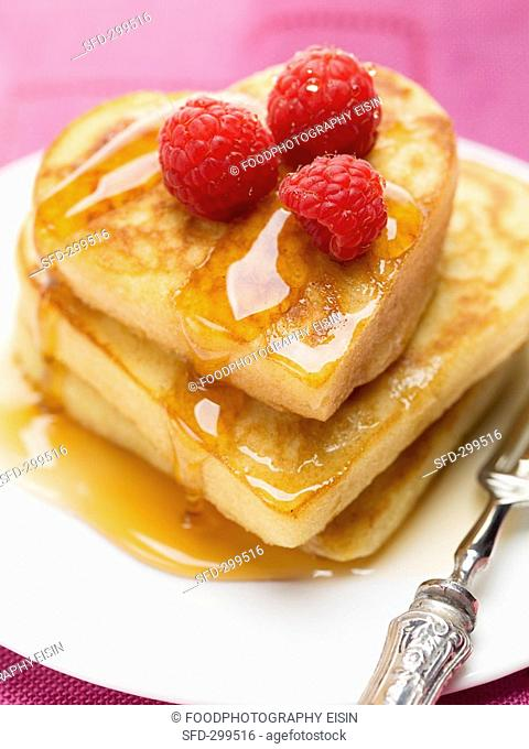 Heart-shaped pancakes with maple syrup and raspberries