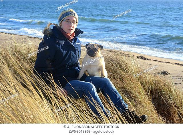 Young woman sit with a pug dog on a dry grass on a beach in Ystad, Scania, Sweden