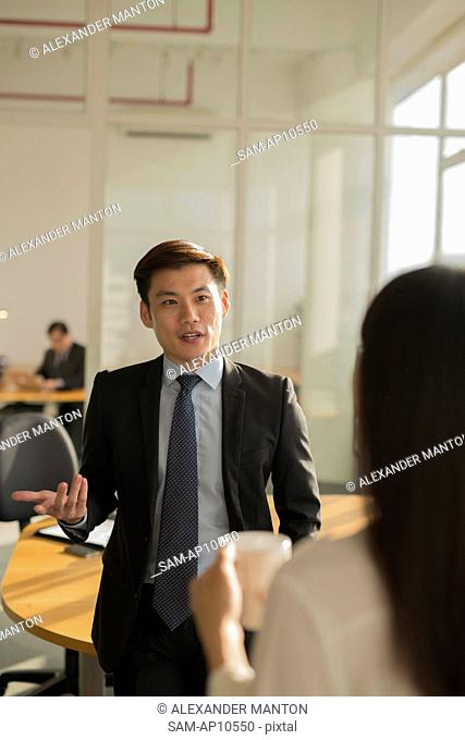 Singapore, Businessman talking to female colleague with senior businessman in background