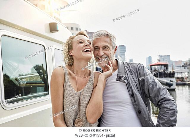 Happy older man and young woman on jetty next to yacht