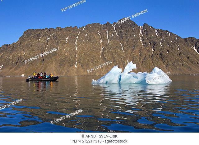 Eco-tourists in zodiac boat photographing melting iceberg in the Lilliehöökfjorden, fjord branch of Krossfjorden in Albert I Land, Spitsbergen, Svalbard, Norway