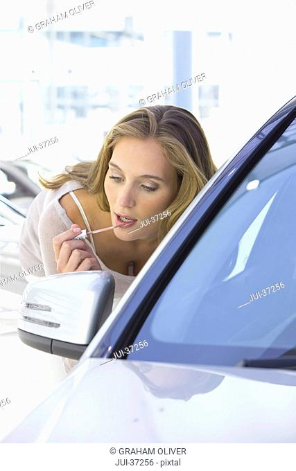 Woman applying lip gloss in side-view mirror of car in car dealership showroom