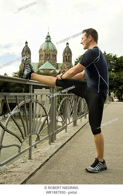 Young man stretching on bridge, Munich, Bavaria, Germany