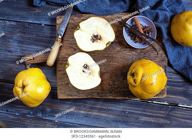 Quince, whole and sliced, on a wooden board
