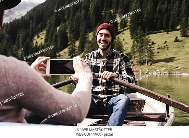 Austria, Tyrol, Alps, woman taking cell phone picture of smiling man in rowing boat on mountain lake