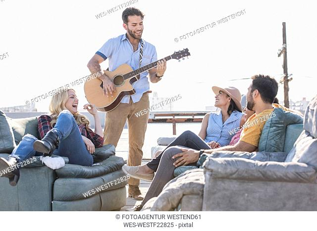 Friends having a rooftop party and playing guitar