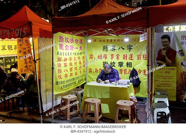 Chinese fortune tellers and palm readers in a lit tent, Temple Street Night Market, Yau Ma Tei, Kowloon, Hong Kong, China