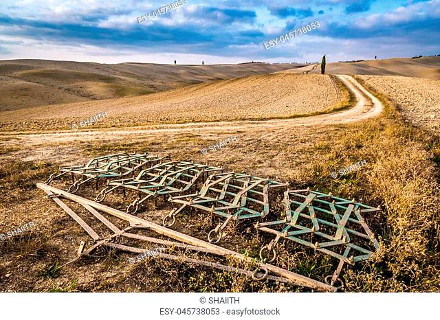 Harrows on a brown field in Tuscany at autumn