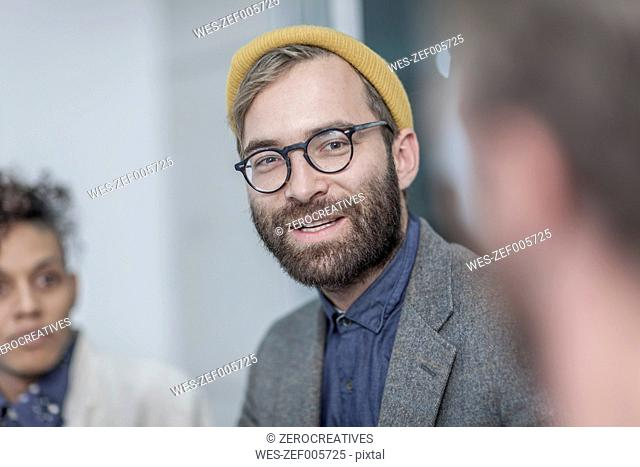 Man with glasses and yellow beanie in meeting with collegues