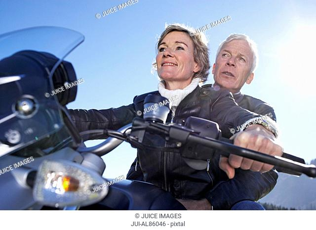 Low angle view of senior couple riding motorcycle