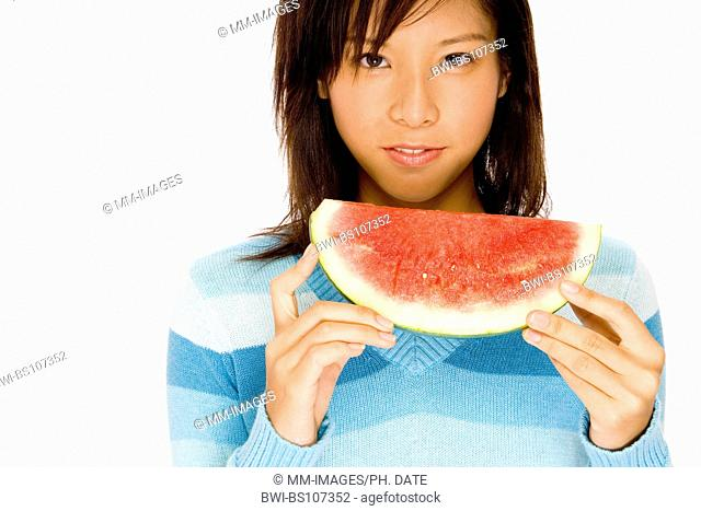 A cute young Asian woman eats a big slice of watermelon