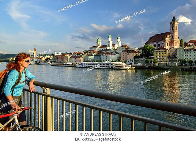Cyclist looking over Danube river to Passau, Lower Bavaria, Germany