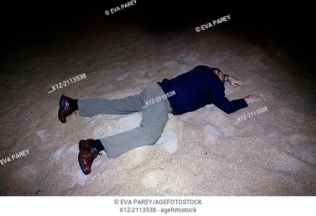 A man lying on the sand of the beach in winter. Barcelona, Spain
